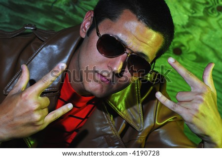 Nightlife portrait of a young man looking (maybe a little too) hip in his aviator sunglasses and super expensive pleather jacket