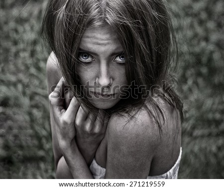 Nightmare and Halloween theme: portrait of scary girl witch in the woods - stock photo