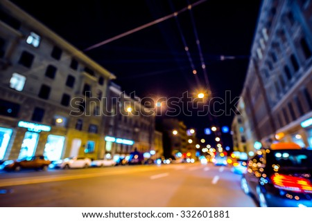 Nights lights of the big city, night avenue in the light of lanterns and headlights of the approaching cars. Wide-angle view, defocused image, image in the blue toning