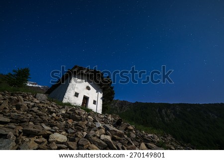Nightscape of an old rural chapel illuminated by natural moolight. Glowing starry sky. Wide angle view from below high in the italian Alps. Boulders in the foreground. - stock photo