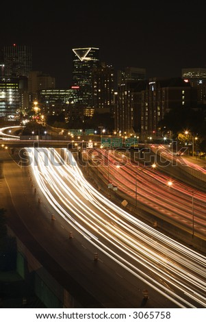 Nightscape of Atlanta, Georgia skyline with blurred automobile lights on highway in foreground.
