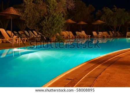 nightshot of a swimming pool and sun chairs - stock photo