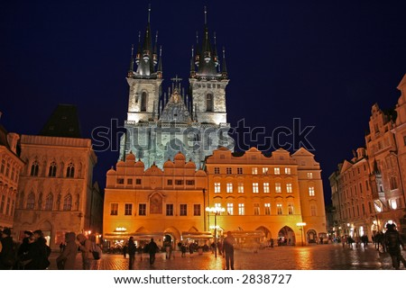 Nighttime shot of Our Lady Before Tyn looming over the lit Old Town Square in Prague - stock photo
