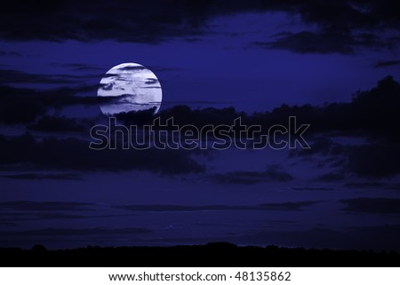 Nighttime sky with big moon and clouds. Ideal for background. - stock photo