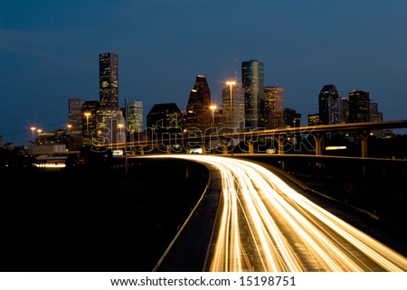 Nighttime traffic out of the city center with skyline and blue sky - stock photo