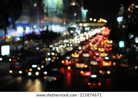 Nighttime View of Defocused Lights of Traffic on a Busy City Road - stock photo