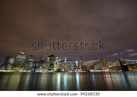 Nighttime view of Lower Manhattan skyline with Brooklyn Bridge in New York City