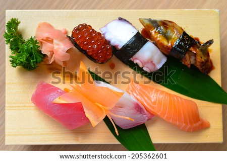 Nigiri sushi set on wooden plate - stock photo