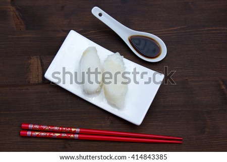Nigiri with halibut on a wooden table seen from above