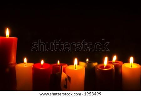 nine candles arranged as Hanukkah menorah (chanukia) with dreidel leaning against them - stock photo
