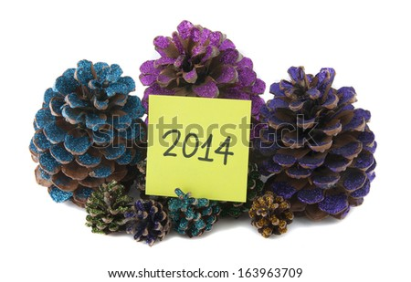 nine christmas pinecones painted with colored glitter and new year paper - stock photo