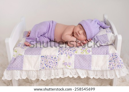 Nine day old newborn baby girl sleeping on a tiny white bed with pillow and patchwork quilt. She is wearing lilac colored pajamas with sleeping cap. - stock photo