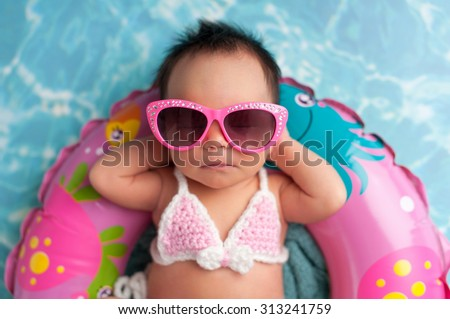 Nine day old newborn baby girl wearing pink sunglasses and a pink and white bikini. She is sleeping on a tiny inflatable swim ring.  - stock photo