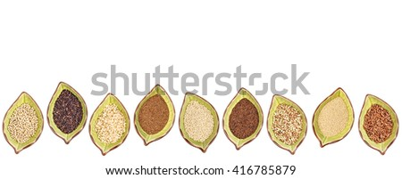 nine gluten free grains (millet, black quinoa, buckwheat, amaranth, teff, sorghum, kaniwa,  and brown rice) - a row of leaf shaped ceramic bowls isolated on white - stock photo