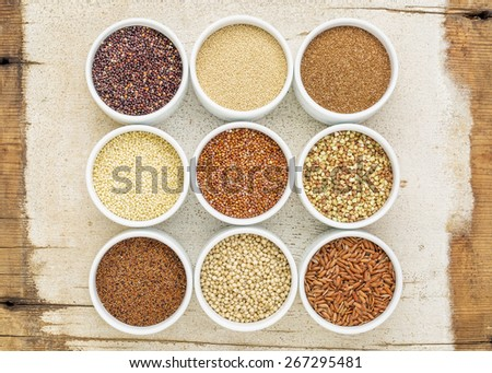 nine healthy, gluten free grains (quinoa, brown rice, millet, amaranth, teff, buckwheat, sorghum), kaniwa), top view of small round bowls against rustic barn wood - stock photo