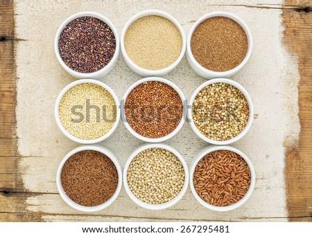 nine healthy, gluten free grains (quinoa, brown rice, millet, amaranth, teff, buckwheat, sorghum), kaniwa), top view of small round bowls against rustic barn wood - stock photo