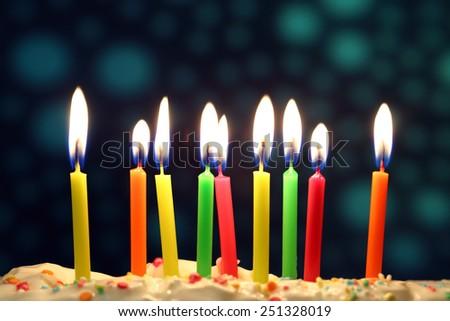 Nine lit birthday candles close up, shallow dof - stock photo