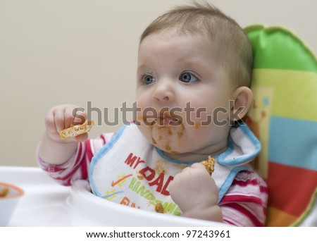 Nine month old baby learning to feed herself. - stock photo