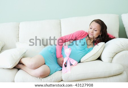 Nine month pregnant beautiful woman holding her belly - stock photo