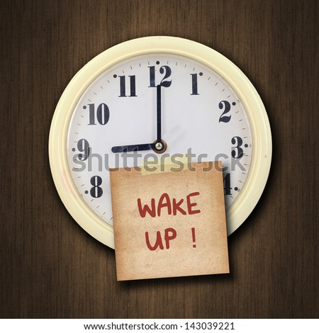 nine o'clock on the wall clock  with the old paper short note and text wake up on wood background - stock photo