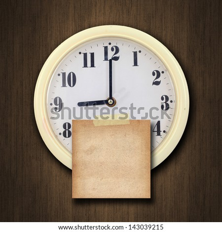 nine o'clock on the wall clock  with the old paper short note on wood background - stock photo