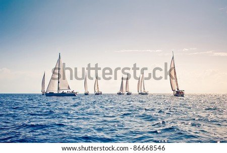Nine sailing ship yachts with white sails in a row - stock photo