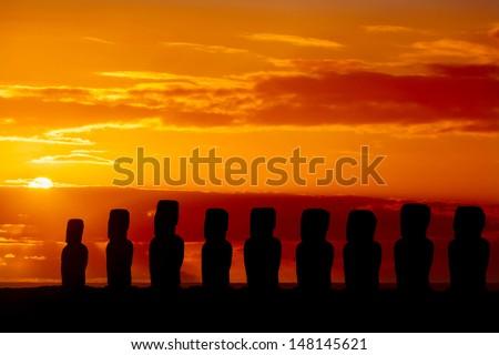 Nine standing moais in orange sunset in Easter Island - stock photo