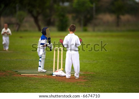 nine year old boys playing cricket, bowler running in but keeper is not focused on the game.