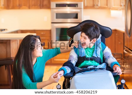 Nine year old disabled boy in wheelchair laughing with teen sister in kitchen - stock photo