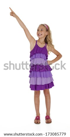 Nine year old girl in purple dress pointing upward on white background. - stock photo