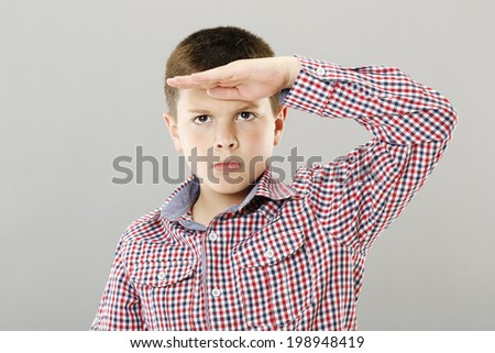 Nine years old boy looking far away - stock photo
