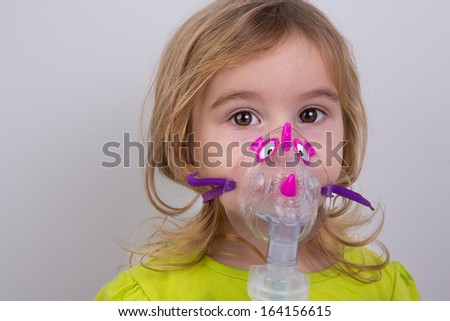 Nine years old kid with allergic asthma, inhaling her medication through spacer while looking at with her tired eyes - stock photo