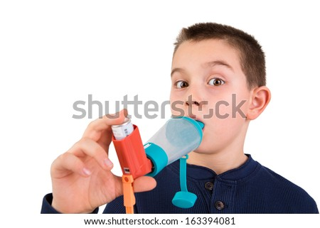 Nine years old kid with allergic asthma, inhaling his medication through spacer while looking at with his wide opened eyes perhaps he is getting energy boost - stock photo