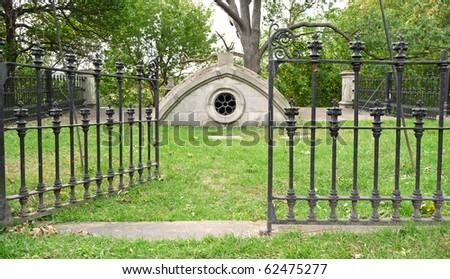 Nineteenth century below ground mausoleum with open gate - stock photo