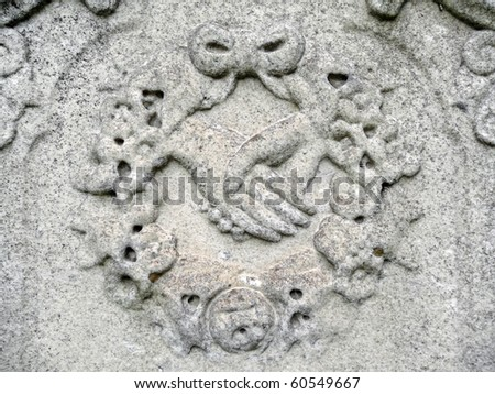 Nineteenth century gravestone detail hands clasped in wreath bas-relief - stock photo