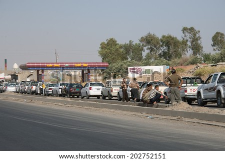 NINEVEH PROVINCE, IRAQ - JUNE 21: Cars wait in line for fuel due to rationing imposed by the Kurdish government in Nineveh Province, northern Iraq, June 21, 2014.  - stock photo