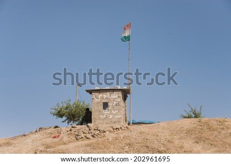 NINEVEH PROVINCE, IRAQI KURDISTAN - JUNE 21: A military post of the Kurdish army or peshmerga forces sits atop a hillside in Ninevah Province, Iraqi Kurdistan, June 21, 2014. - stock photo