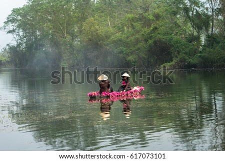 Ninh Binh, Vietnam - Oct 9, 2016: River scene with smoke, a boat carrying girls wearing traditional dress Ao Dai, conical hat, and flower, in Yen stream