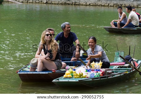 "NINHBINH, VIETNAM - May 17, 2015: Unidentified Vietnamese persons on the Floating Market at ""Ngo Dong"" river in Tam Coc Bich Dong heritage, NinhBinh province, Vietnam."