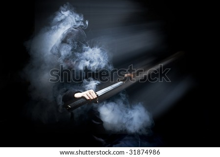 Ninja in action with sword at night in smoke - stock photo