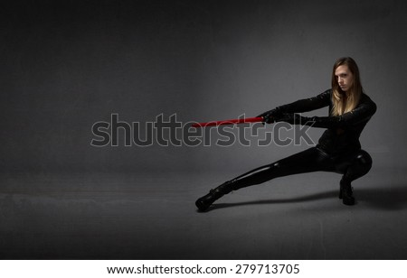 ninja with sword on hand, dark background - stock photo