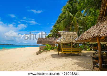 Nipa Huts On A Tropical Island Beach