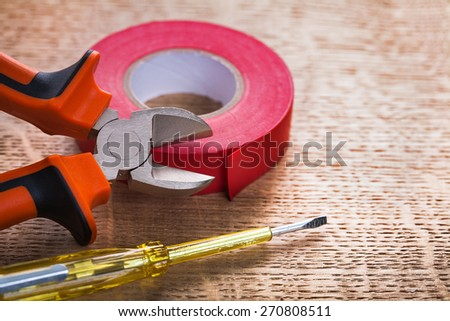 nippers tester roll of red insulating tape on wooden board construction concept  - stock photo