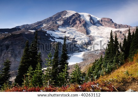 Nisqually glacier at Mount Rainier park. first snow of the season in the foreground amidst fall colors - stock photo