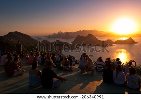 NITEROI, RJ, BRAZIL - APRIL 6: People watch sunset on 6 April, 2014 in the City Park of Niteroi. Every sunny day many people gather here to watch the sun go down behind the hills of Rio de Janeiro. - stock photo
