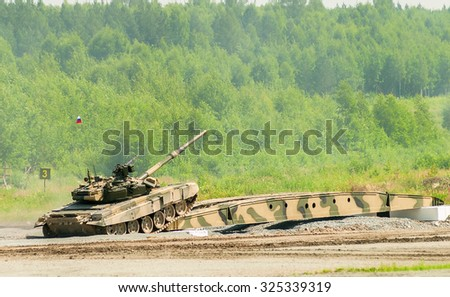 Nizhniy Tagil, Russia - July 12. 2008:  T-80 tank drives on bridge induced through obstacle. Display of military equipment of land forces. RAE exhibition