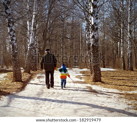 Nizhny Novgorod region, Russia - March 2014:Grandfather and grandson are walking in spring park