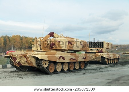 NIZHNY TAGIL, RUSSIA - SEP 26, 2013: The exhibition RUSSIA ARMS EXPO (RAE-2013). Russian Heavy Flame Thrower System, multiple rocket launcher TOS-1 and Transport-loading machine