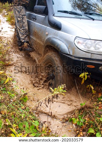 NIZHNY TAGIL. RUSSIA - SEPTEMBER 22, 2012: Russian Plain Road in the heart of Siberia. Flailing at breakneck speed wheel off-road vehicle stuck in a swamp - stock photo