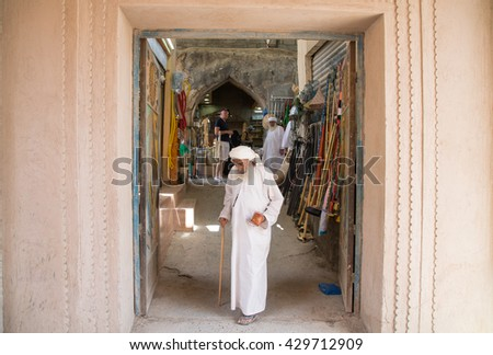Nizwa, Oman - circa May 2016: old Omani man walking out of the old Nizwa market